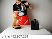 Trendy barista girl brewing filter coffee. Wood drip station. Red patent leather skirt, black t-shirt. Gooseneck kettle. Стоковое фото, фотограф Кристина Сорокина / Фотобанк Лори