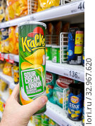 Купить «Russia Samara December 2019: Hand holds a package of chips on the background of a rack with chips in a supermarket. Text in Russian: with the taste of sour cream and onions.», фото № 32967620, снято 25 декабря 2019 г. (c) Акиньшин Владимир / Фотобанк Лори