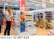 Купить «Russia Samara November 2019: A young woman chooses shampoo in a store in the department of perfumes and cosmetics. Text in Russian: discount», фото № 32967624, снято 25 декабря 2019 г. (c) Акиньшин Владимир / Фотобанк Лори
