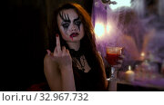 Girl with makeup for Halloween is sitting in front of a mirror. Woman drinks a red drink from a glass and shows her middle finger. Стоковое видео, видеограф Константин Мерцалов / Фотобанк Лори