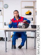 Young male contractor repairing vacuum cleaner at workshop. Стоковое фото, фотограф Elnur / Фотобанк Лори