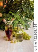 Купить «Bottles of wine and a bunch of grapes on a table close-up», фото № 32968124, снято 13 октября 2014 г. (c) Татьяна Ляпи / Фотобанк Лори