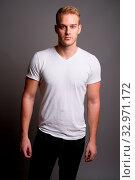 Купить «Studio shot of young handsome man with blond hair wearing white shirt against gray background», фото № 32971172, снято 25 января 2020 г. (c) easy Fotostock / Фотобанк Лори