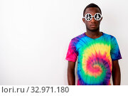Купить «Studio shot of young serious black African man hippie wearing sunglasses with peace sign against white background», фото № 32971180, снято 26 января 2020 г. (c) easy Fotostock / Фотобанк Лори