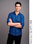 Купить «Studio shot of young handsome businessman wearing blue shirt against gray background», фото № 32971184, снято 25 января 2020 г. (c) easy Fotostock / Фотобанк Лори