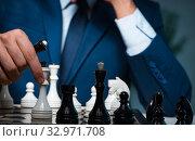 Купить «Businessman playing chess in strategy concept», фото № 32971708, снято 9 октября 2017 г. (c) Elnur / Фотобанк Лори