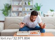 Купить «Man eating pizza having a takeaway at home relaxing resting», фото № 32971804, снято 18 июля 2017 г. (c) Elnur / Фотобанк Лори