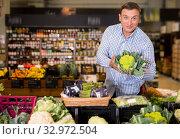 Купить «Portrait of man choosing broccoli in supermarket», фото № 32972504, снято 9 октября 2019 г. (c) Яков Филимонов / Фотобанк Лори