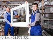Купить «Production workers in coverall with different finished PVC profiles and windows at factory», фото № 32972532, снято 30 марта 2017 г. (c) Яков Филимонов / Фотобанк Лори