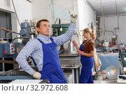 Купить «Male glazier working with glass on drilling machine», фото № 32972608, снято 10 сентября 2018 г. (c) Яков Филимонов / Фотобанк Лори