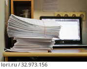Купить «Стопка бумаг, перетянутая резинкой, лежит на столе в медицинском учреждении, на заднем плане светящийся монитор компьютера», фото № 32973156, снято 23 января 2020 г. (c) Игорь Тарасов / Фотобанк Лори
