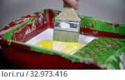 Купить «A person mixing white and yellow colors in the paint tray», видеоролик № 32973416, снято 3 июня 2020 г. (c) Константин Шишкин / Фотобанк Лори