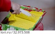 Купить «A person covering a roller in yellow paint in the paint tray», видеоролик № 32973508, снято 3 июня 2020 г. (c) Константин Шишкин / Фотобанк Лори