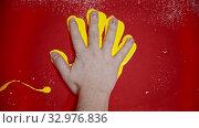 Купить «Putting a hand imprint with a bright yellow color on the red wall», видеоролик № 32976836, снято 24 января 2020 г. (c) Константин Шишкин / Фотобанк Лори