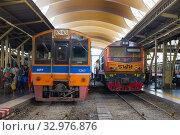 Два пассажирских поезда на главном железнодорожном вокзале Hua Lamphong. Бангкок, Таиланд (2019 год). Редакционное фото, фотограф Виктор Карасев / Фотобанк Лори
