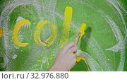 """Купить «A person writing """"COLOR"""" on the green wall with a yellow paint», видеоролик № 32976880, снято 24 января 2020 г. (c) Константин Шишкин / Фотобанк Лори"""