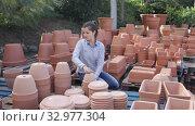 Купить «Portrait of female worker of gardening material warehouse checking clay pots», видеоролик № 32977304, снято 8 ноября 2019 г. (c) Яков Филимонов / Фотобанк Лори