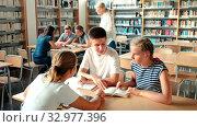 Купить «Teenage group of pupils sitting at table and studying, teacher in classroom», видеоролик № 32977396, снято 27 мая 2020 г. (c) Яков Филимонов / Фотобанк Лори