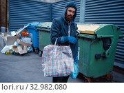 Купить «Male bearded beggar searching food in trashcan», фото № 32982080, снято 26 октября 2019 г. (c) Tryapitsyn Sergiy / Фотобанк Лори