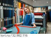 Купить «Seamstress measures the fabric in textile store», фото № 32982116, снято 8 ноября 2019 г. (c) Tryapitsyn Sergiy / Фотобанк Лори