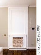 Декоративный камин на стене - современный интерьер. Белое обрамление и красный кирпич. Стоковое фото, фотограф Elizaveta Kharicheva / Фотобанк Лори
