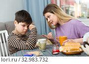 Купить «Upset mother and unhappy son arguing during breakfast indoors», фото № 32983732, снято 9 февраля 2019 г. (c) Яков Филимонов / Фотобанк Лори