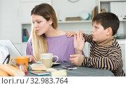 Купить «Young mother working at laptop and unhappy preteen son», фото № 32983764, снято 9 февраля 2019 г. (c) Яков Филимонов / Фотобанк Лори