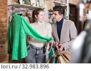 Купить «Young female with male are looking on green jacket for her», фото № 32983896, снято 12 марта 2018 г. (c) Яков Филимонов / Фотобанк Лори