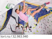Купить «Mountaineer climbing artificial rock wall without belay», фото № 32983940, снято 25 февраля 2020 г. (c) Яков Филимонов / Фотобанк Лори