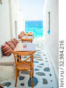 Benches with pillows in a typical greek outdoor cafe in Mykonos with amazing sea view on Cyclades islands. Стоковое фото, фотограф Дмитрий Травников / Фотобанк Лори