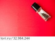 Купить «Pepper peas in a glass jar on a red background», фото № 32984244, снято 10 августа 2019 г. (c) Катерина Белякина / Фотобанк Лори