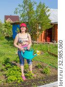молодая красивая женщина спальником в руках на своём дачном участке. Стоковое фото, фотограф Акиньшин Владимир / Фотобанк Лори