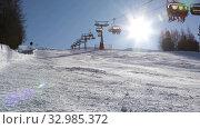 Купить «Chairlift lifts skiers up the mountain above an empty ski slope in the rays of the sun. Livigno, Italy», видеоролик № 32985372, снято 27 января 2020 г. (c) Алексей Кузнецов / Фотобанк Лори