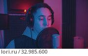 Купить «A man rapping through the pop-filter in the microphone - neon lighting», видеоролик № 32985600, снято 4 июля 2020 г. (c) Константин Шишкин / Фотобанк Лори