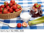 Ein Korb Erdbeeren, ein Einkochglas mit fertiger Erdbeermarmelade, Zucker, ein Kochlöffel und aufgeschnittene Erdbeeren liegen auf einer karierten Tischdecke bereit. Стоковое фото, фотограф Zoonar.com/Photographer: Olaf Schulz / easy Fotostock / Фотобанк Лори