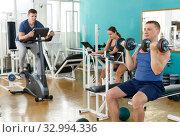 Купить «Portrait of man lifting dumbbells at gym», фото № 32994336, снято 5 ноября 2018 г. (c) Яков Филимонов / Фотобанк Лори