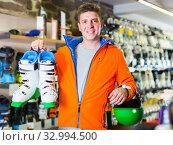 Купить «Adult man in jacket and helmet is demonstrating his choice of boots for skiing.», фото № 32994500, снято 31 июля 2017 г. (c) Яков Филимонов / Фотобанк Лори