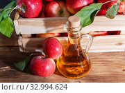 Купить «Homemade fruit canning, diet healthy food and drink. Apple cider vinegar, juice, salad dressing from a crop of ripe red garden fruits in a glass jug on a wooden rustic background», фото № 32994624, снято 22 сентября 2019 г. (c) Светлана Евграфова / Фотобанк Лори