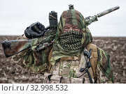 Купить «Army marksman, airsoft player in camouflage uniform and load carrier, masking cape on head, armed service rifle with optical sight, hiding face with shemagh, standing on field, looking into distance.», фото № 32998532, снято 26 ноября 2017 г. (c) easy Fotostock / Фотобанк Лори