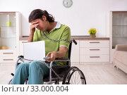 Купить «Young male invalid in wheel-chair suffering at home», фото № 33000004, снято 23 июля 2019 г. (c) Elnur / Фотобанк Лори