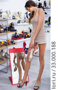 Купить «girl customer trying on chosen shoes in footwear department», фото № 33000188, снято 17 февраля 2020 г. (c) Яков Филимонов / Фотобанк Лори