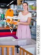 Pleasant pregnant woman choosing chair for feeding baby at infant shop. Стоковое фото, фотограф Яков Филимонов / Фотобанк Лори