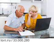 Mature man and woman discussing while looking at laptop together. Стоковое фото, фотограф Яков Филимонов / Фотобанк Лори