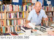 Купить «Older man choosing books in bookstore», фото № 33000380, снято 11 июня 2018 г. (c) Яков Филимонов / Фотобанк Лори