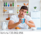 Man falling asleep during his breakfast after overtime work. Стоковое фото, фотограф Elnur / Фотобанк Лори
