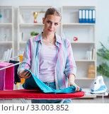 Купить «Happy housewife doing ironing at home», фото № 33003852, снято 28 июня 2017 г. (c) Elnur / Фотобанк Лори