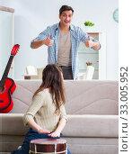 Купить «Young family singing and playing music at home», фото № 33005952, снято 30 января 2018 г. (c) Elnur / Фотобанк Лори