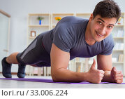 Купить «Young man exercising at home in sports and healthy lifestyle con», фото № 33006224, снято 3 мая 2017 г. (c) Elnur / Фотобанк Лори