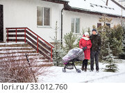 Loving young couple with baby stroller standing next to their house at winter season during snowfall. Стоковое фото, фотограф Кекяляйнен Андрей / Фотобанк Лори