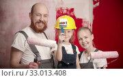 Купить «Happy family are looking at the camera smiling and raises paint rollers and brush», видеоролик № 33013408, снято 3 июня 2020 г. (c) Константин Шишкин / Фотобанк Лори